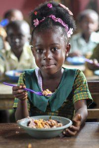 Flicka äter i Ghana
